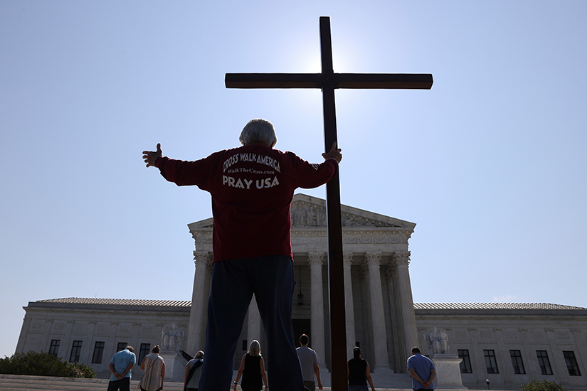 A demonstrator in Washington held a large cross outside the U.S. Supreme Court July 8.
