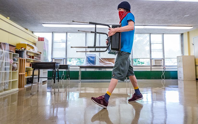 Billy Dugan arranged desks to conform to social distancing requirements at St. Mary Magdalen School in Brentwood on July 21. Catholic schools in the archdiocese are releasing plans for returning to in-person learning, with social distancing an important aspect of many plans.