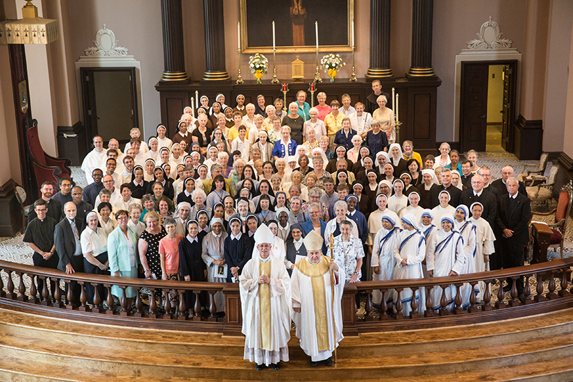 Archbishop Robert J. Carlson and then-Auxiliary Bishop Edward M. Rice posed for a picture with men and women religious after a Mass celebrating consecrated life in 2014, the 250th anniversary of the founding of St. Louis.