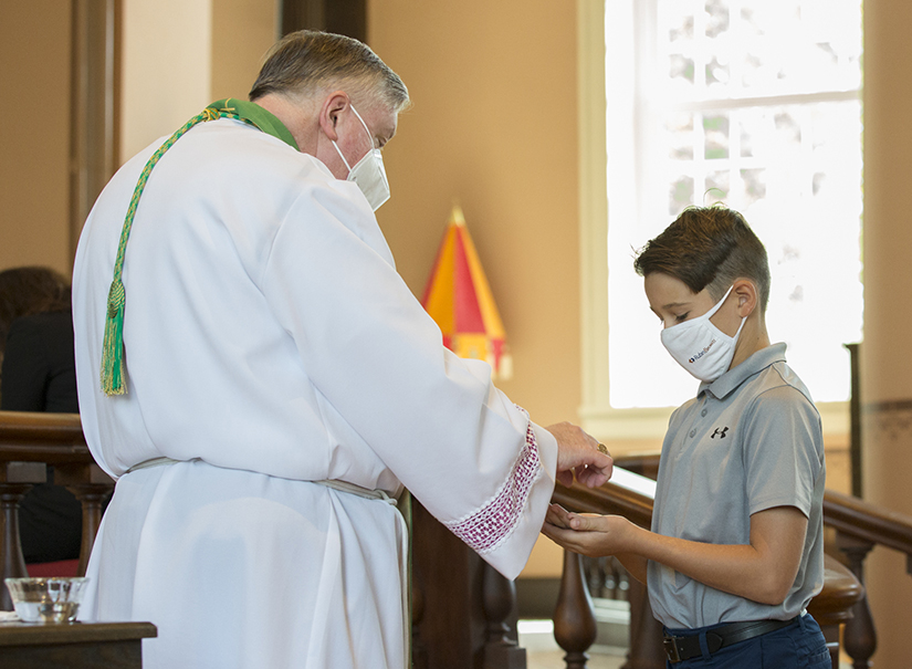 Nicholas Sackman, 10, received Holy Communion after Mass on Aug. 30 from Archbishop Mitchell Rozanski at the Basilica of Saint Louis, King of France (Old Cathedral).