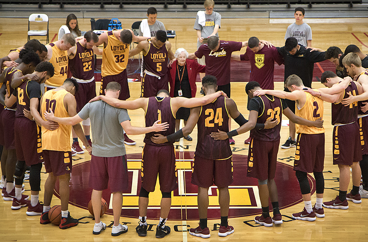 Sister Jean Dolores Schmidt, 98, longtime chaplain of the Loyola University Chicago men's basketball team and campus icon, prayed with the team in October 2017. Sister Jean credited pregame prayer and the players' solid teamwork for the Ramblers' thrilling last-second 64-62 NCAA Tournament win over the University of Miami March 15.