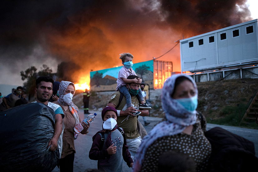 Displaced people fled after fires broke out at the Moria refugee camp on the island of Lesbos, Greece, Sept. 9. The camp, which was mostly destroyed, was home to at least 12,000 people, six times its maximum capacity of just over 2,000 asylum-seekers.