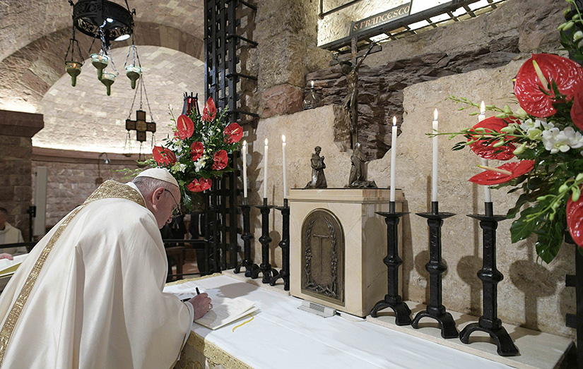 "Pope Francis signed his new encyclical, ""Fratelli Tutti, on Fraternity and Social Friendship"" after celebrating Mass at the Basilica of St. Francis in Assisi, Italy, Oct. 3."