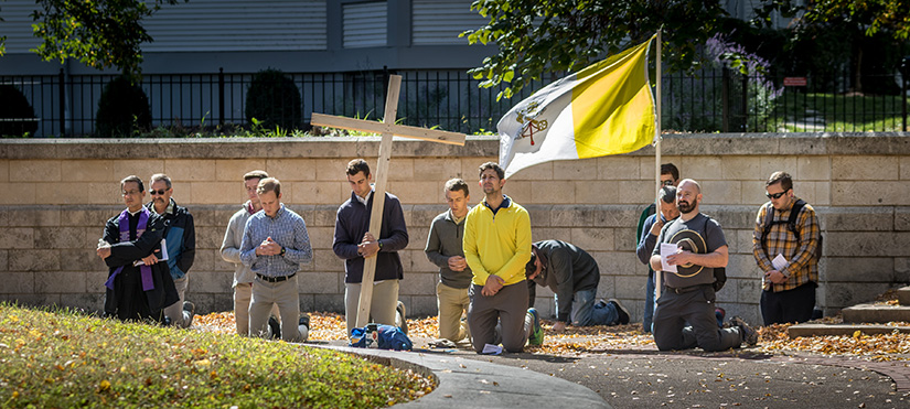 Pilgrims in the Joseph Challenge knelt in prayer after they arrived at their final destination at the Shrine of St. Joseph Downtown on Oct. 4. The men walked 24 miles from St. Joseph Church in Manchester to the shrine, taking time for prayer, reflection and fellowship along the way.