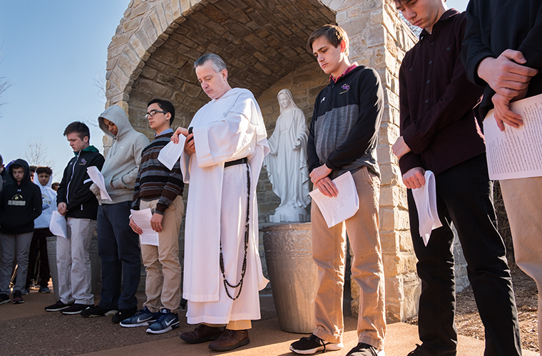 Father DePorres Durham, OP, timed 100 seconds of silence for victims of gun violence while praying with students March 14 at Christian Brothers College High School in Town and Country. Students gathered around the Marian grotto at the school to pray as part of the national movement of school walkouts to call for gun policy reform and the end of violence.