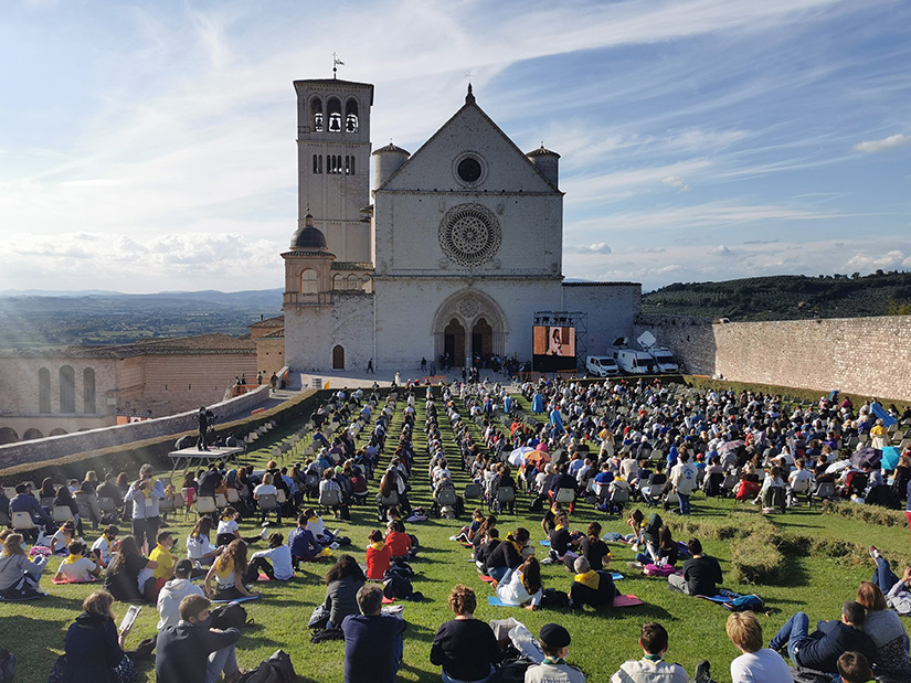People sat outside the Basilica of St. Francis in Assisi for the beatification Mass of Carlo Acutis in Assisi, Italy, Oct. 10. The Mass was held inside the basilica but measures to prevent the spread of COVID-19 meant that most of the attendees sat outside.