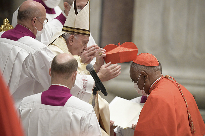 Pope Francis placed the red biretta on new Cardinal Wilton D. Gregory of Washington during a consistory for the creation of 13 new cardinals in St. Peter's Basilica at the Vatican Nov. 28.