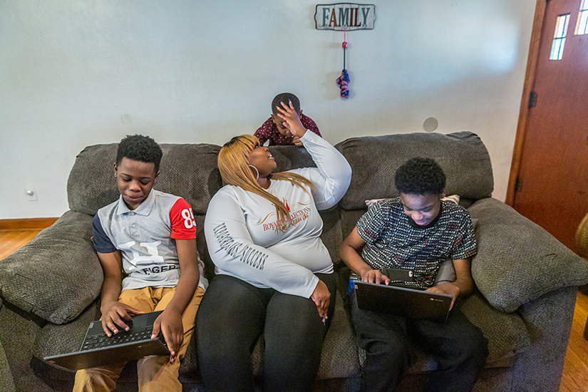 Dawn Cotton has been assisted several times by Catholic Charities federated agencies. She helped her sons Drentay and Dontay Smith with their schoolwork while son Ace Rimson sought her attention at their St. Louis home.