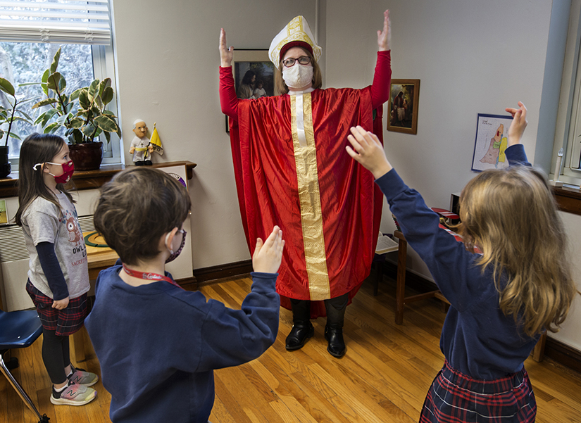 Karen Jaeger dressed up as St. Nicholas to teach students at Sacred Heart Villa School about the real St. Nicholas and the symbolism of the candy cane on Dec. 4. From left are 5-year-old students Winifred Frisch, Thomas McCabe and Dervla Sheehan.