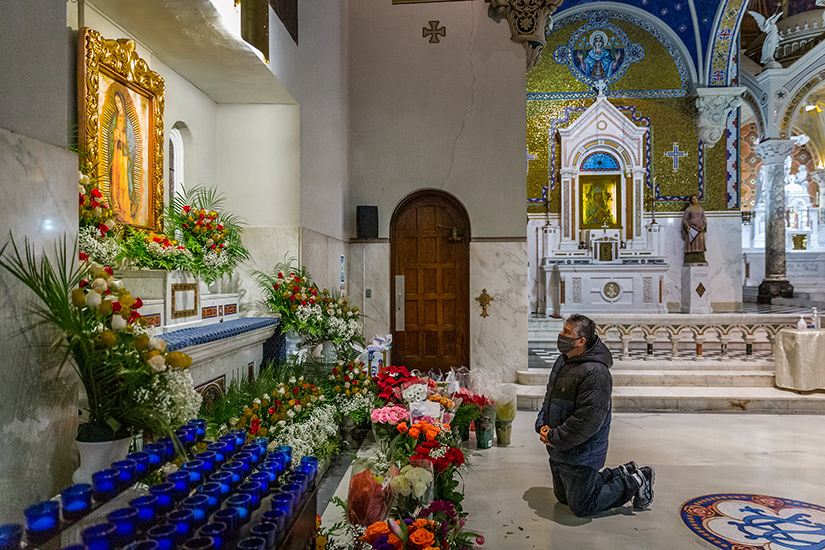 Luis Ortiz knelt in front of a shrine full of flowers as parishioners celebrated the feast of Our Lady of Guadalupe at St. Cecilia Church in St. Louis Dec. 12. The celebration included songs, prayers, Mass and traditional Mexican treats.