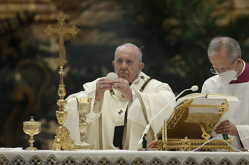 Pope Francis elevated the Eucharist as he celebrated Mass on the feast of the Epiphany in St. Peter's Basilica at the Vatican Jan. 6.