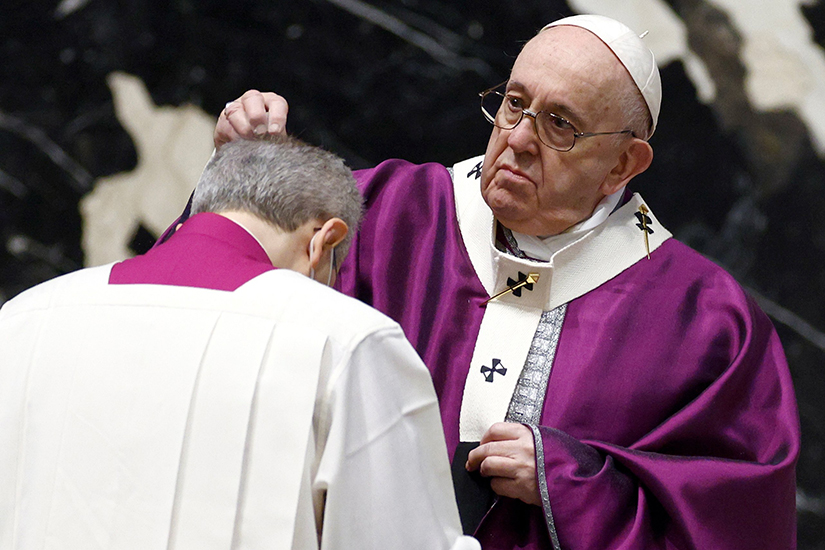 Pope Francis sprinkled ashes on the head of a priest at Ash Wednesday Mass in St. Peter's Basilica at the Vatican Feb. 17.