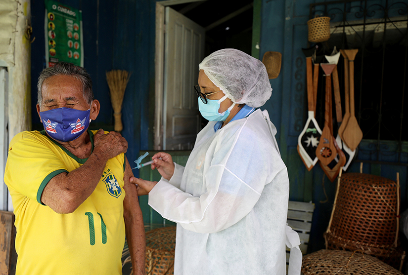 An Indigenous man received the AstraZeneca/Oxford COVID-19 vaccine from a municipal health worker in the Sustainable Development Reserve of Tupe in Manaus, Brazil, Feb. 9.