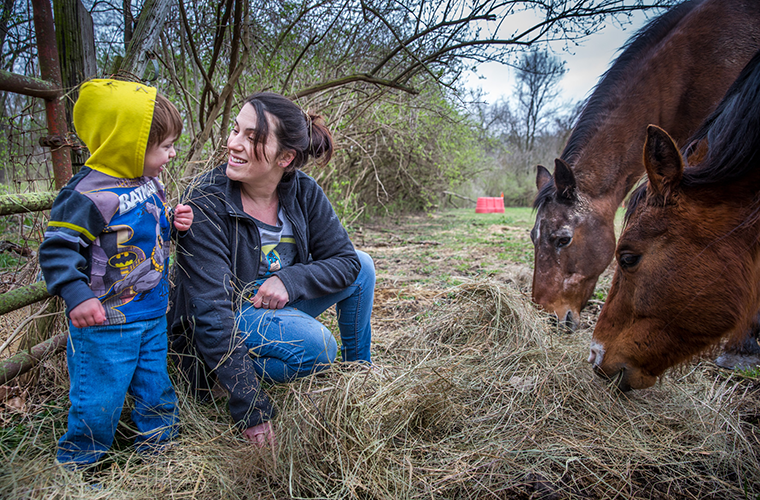 Sally DeIuliis and her son, Emmerson, fed their neighbor's horses in Black Jack on April 15. DeIuliis was six months pregnant with Emmerson and addicted to heroin when she received help from Catholic Charities' Queen of Peace Center and the WISH Clinic at SSM St. Mary's Hospital.