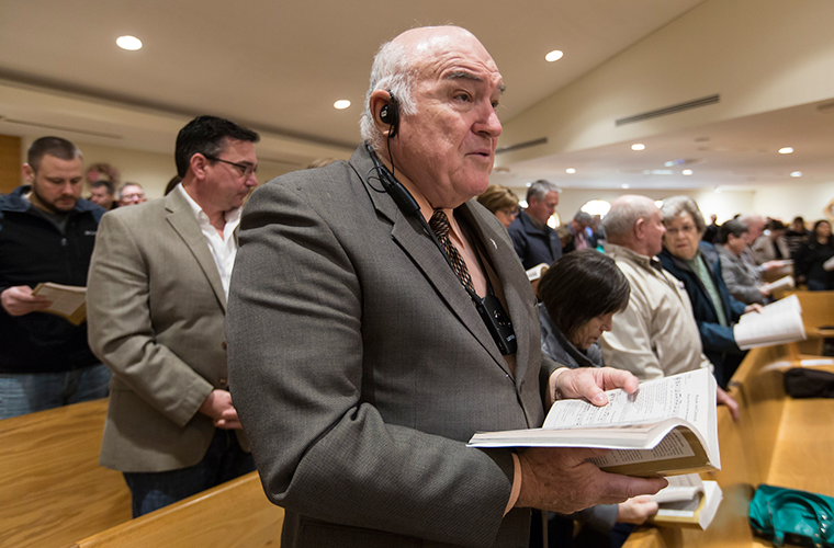 Robert Noonan used a hearing assist device April 8 at Mass at St. Patrick Church in Wentzville. In December, the parish installed a system that includes a radio transmitter to broadcast the church's sound system to people who need assistance hearing.