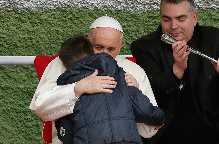 Pope Francis embraced Emanuele, a boy whose father died, as he visited St. Paul of the Cross Parish in Rome April 15. Emanuele hesitated to ask his question, but the pope encouraged him to speak privately to the pope, who then shared his question.