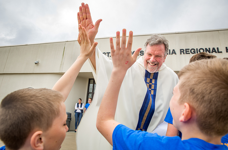 Father Kevin Schmittgens, president at St. Francis Borgia Regional High School, greeted visitors from Catholic schools April 24. Archbishop Robert J. Carlson celebrated Mass at the high school, which invited students from area Catholic grade schools.