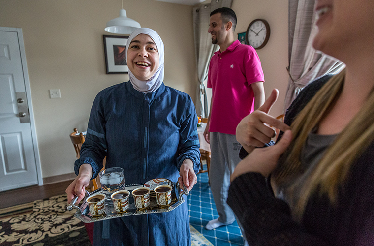 Lina Almuallem brought in a tray of coffee as she talked with Jessica Bueler on the day she was preparing homemade Syrian cuisine in her kitchen in Mapelwood on April 22.