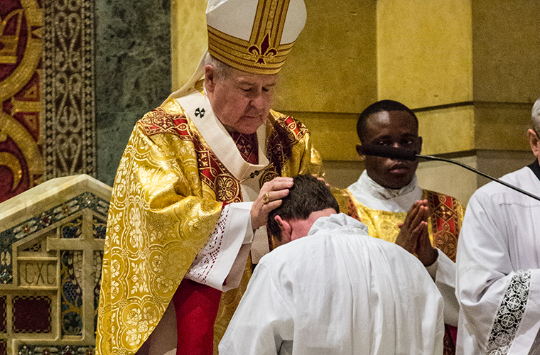 Archbishop Robert J. Carlson laid hands on Deacon Christopher Rubie at his ordination to the transitional diaconate last year.