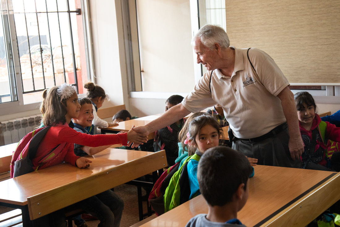 Msgr. Jack Schuler, chaplain at Catholic Charities of St. Louis and pastor of St. Cronan Parish in south St. Louis, greeted students at a class in Lebanon. The school serving refugee children is supported by Catholic Relief Services, the overseas relief and development agency of the U.S. bishops.