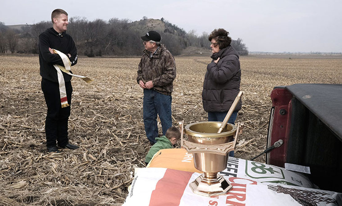 Father Andrew Sohm talked with farmers Marlan and Sherry Rolfes of Newcastle, Neb., after blessing their fields April 11.