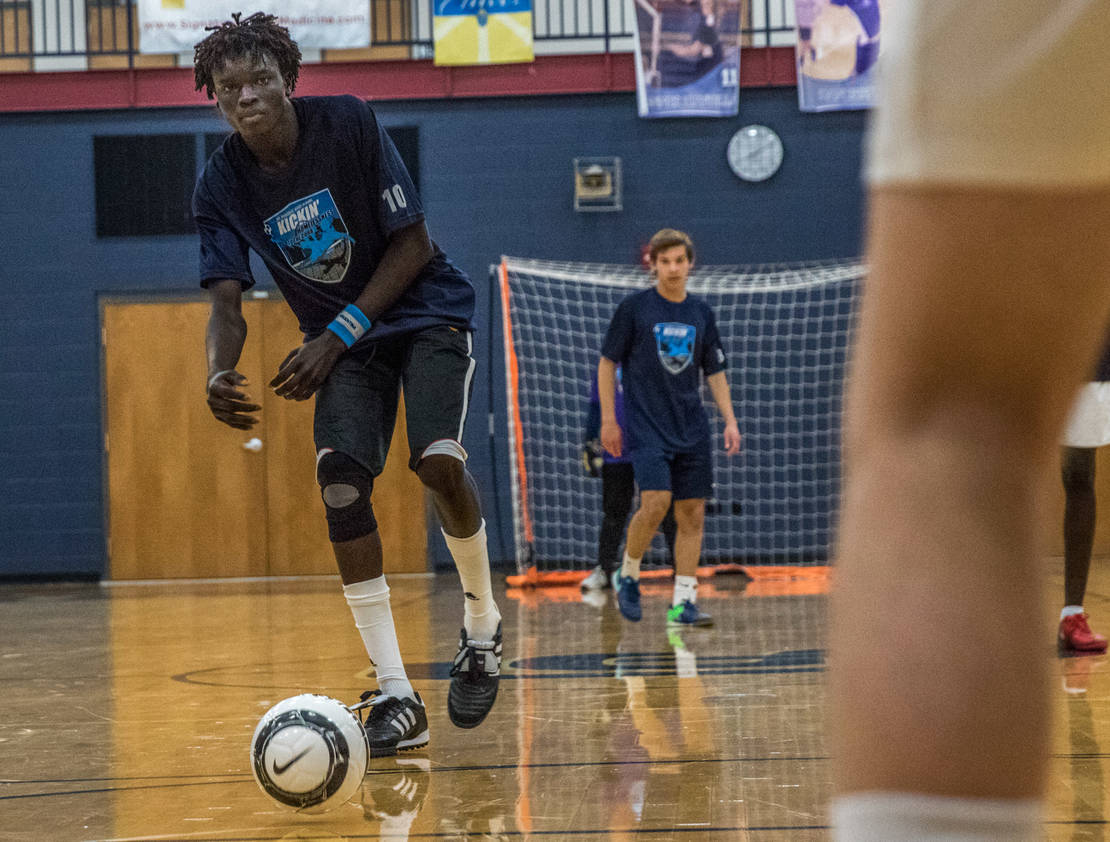 St. Louis Roadies player Chuong Tang, a refugee from South Sudan, kicked the ball during a game against St. Dominic High School soccer players. The St. Louis Roadies, a team comprised of homeless or formerly homeless men and refugees, played against a team from St. Dominic as part of a school project by student Tony Petruso.