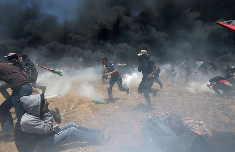 Palestinians ran for cover from Israeli fire and tear gas at the Israel-Gaza border during a protest against the U.S. embassy move to Jerusalem May 14.
