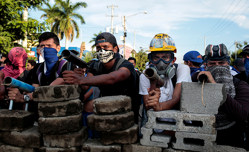 Demonstrators in Managua, Nicaragua, stood behind a barricade during clashes with police May 30. Nicaragua's bishops issued an urgent statement May 31 calling for an end to police and paramilitary attacks on protesters.