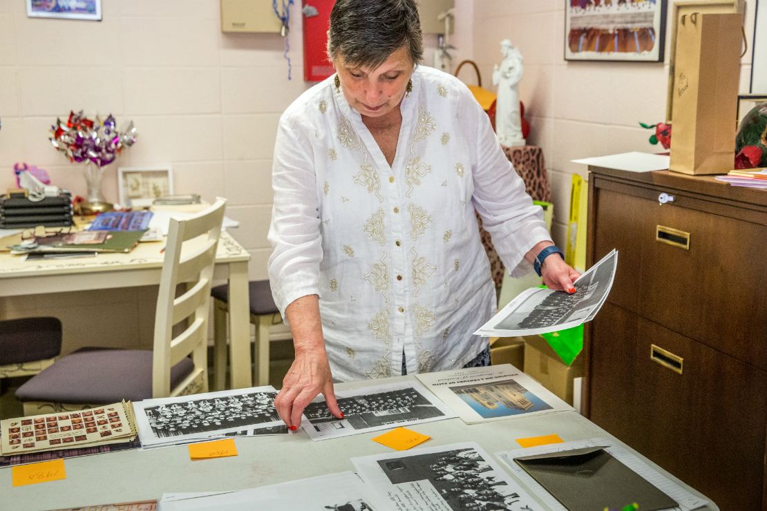 Juliann DePalma Hesed, principal of St. Margaret of Scotland Parish School, organized years of photographs and paraphernalia to be placed inside a time capsule celebrating 100 years of the school.