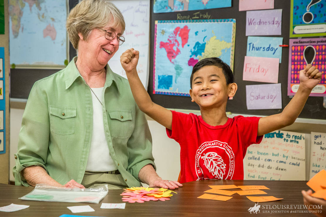"Sister Joan Stoverink, ASC, smiled as kindergarten student David Mung celebrated a victory in a game of ""Go Fish Antonym"" in class on May 21. Sister Joan tutors students at St. Stephen Protomartyr, many of whom are from Myanmar, as part of the English Tutoring Project."