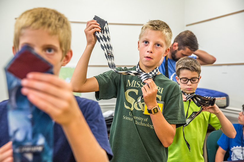 "Daniel Goring, from St. Paul Church in Highland, Ill., learned how to put on tie as part of a session entitled ""How to be a man"" at Kenrick-Glennon Days. The session also included tips for shaving and the importance of a firm handshake."