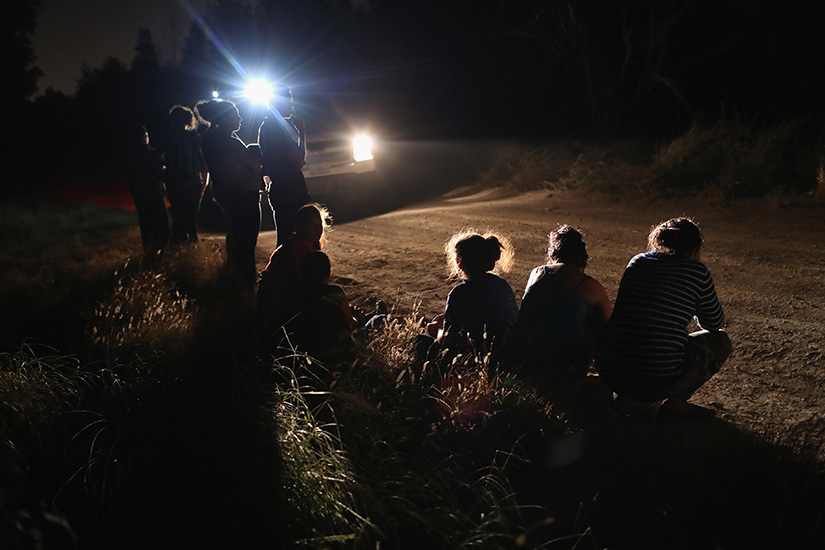 A U.S. Border Patrol vehicle illuminated a group of Central American asylum seekers before taking them into custody near the U.S.-Mexico border on June 12 in McAllen, Texas. The group of women and children had rafted across the Rio Grande from Mexico and were detained by U.S. Border Patrol agents before being sent to a processing center for possible separation.